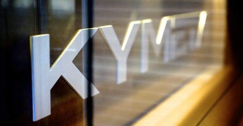 Block white lettering spelling KYMETA on a clear window