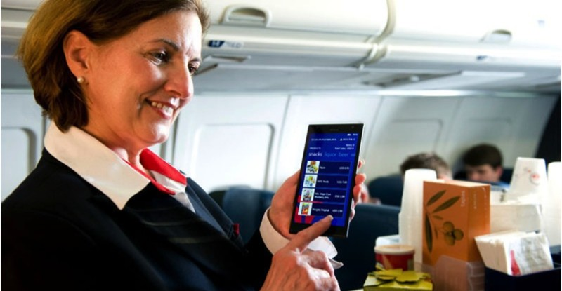 Flight attendant showing a customer duty free sales on mobile device