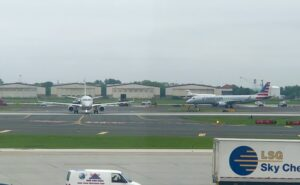 aircraft line up on the runway at a busy airport. A catering truck is also in view