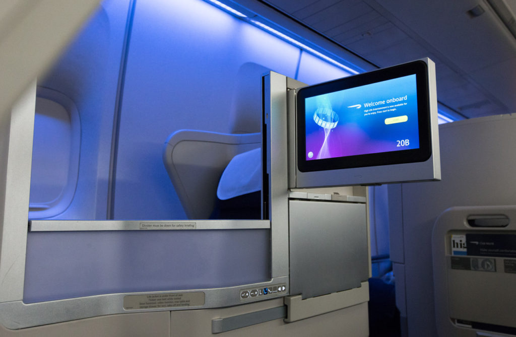 Inside the newly retrofitted BA Boeing 747, showing a large IFE screen, and a business class suite with seat shell. Blue mood lighting adds to the scene