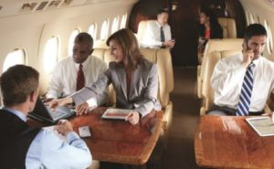 A vairety of business people, two women and 4 men on a private business jet using different electronic devices to access internet.