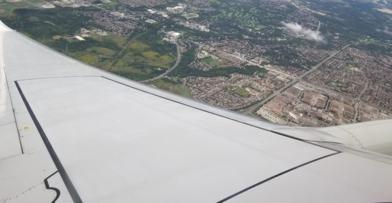Out the aircraft window overlooking the farmland and city.