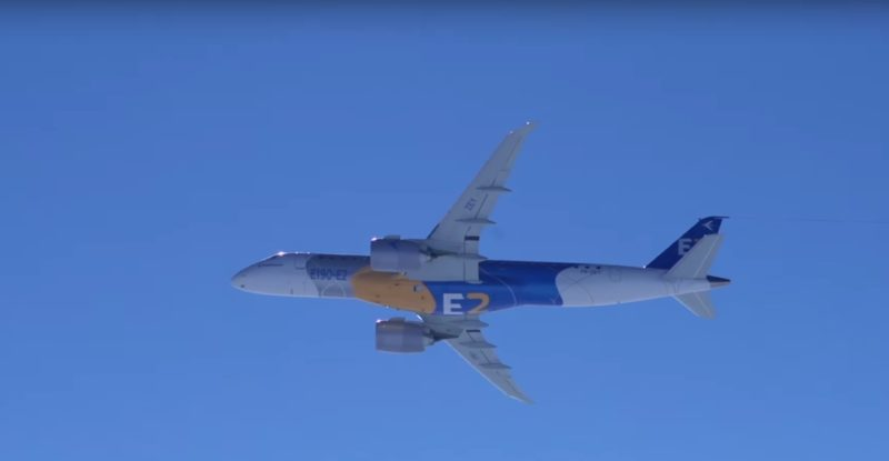 Belly of an Embraer E2 inflight in a clear blue sky.