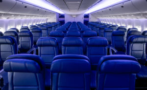 Rows of blue economy class seats on board a Delta 777