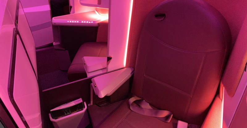 A Safran premium seat bathed in pink LED lighting on board an aircraft