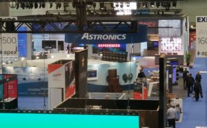 The 2019 APEX EXPO show floor with signage of different PaxEx companies, and attendees walking the halls