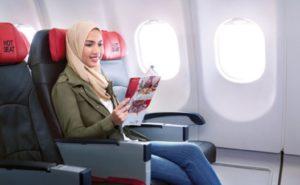 Woman reading the duty free magazine on airasia aircraft