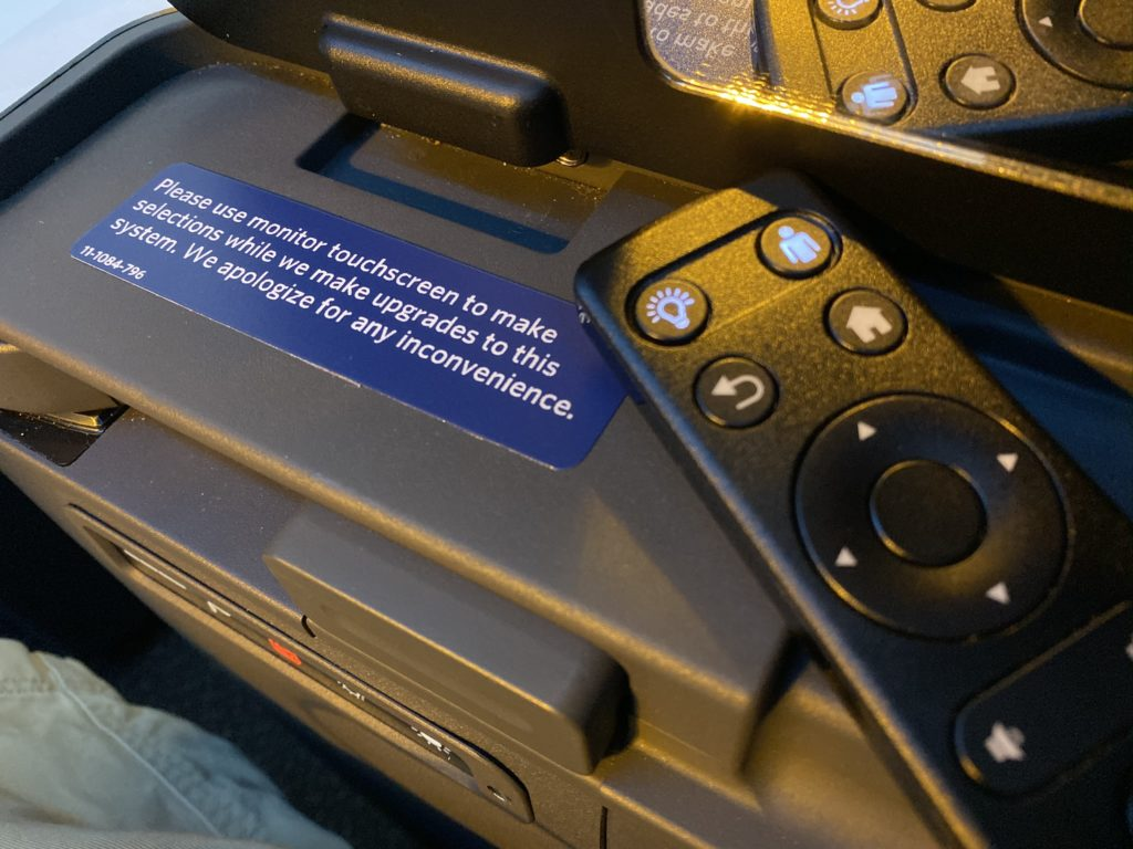 ife remote next to sign that says Please use monitor touchscreen to make selectsion while we make upgrades to this system