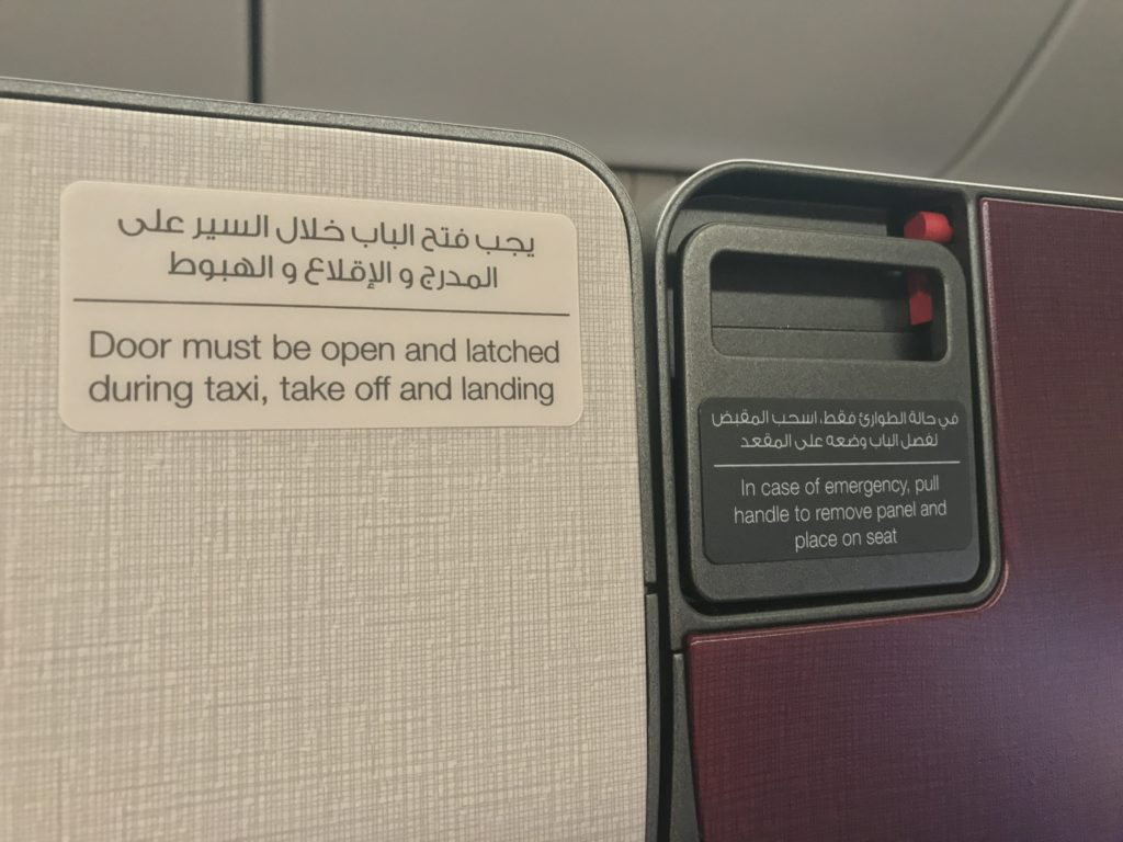 Qatar's Qsuite doors feature a pull-down emergency release. Image: John Walton