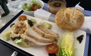 An airline meal tray with turkey and a roll