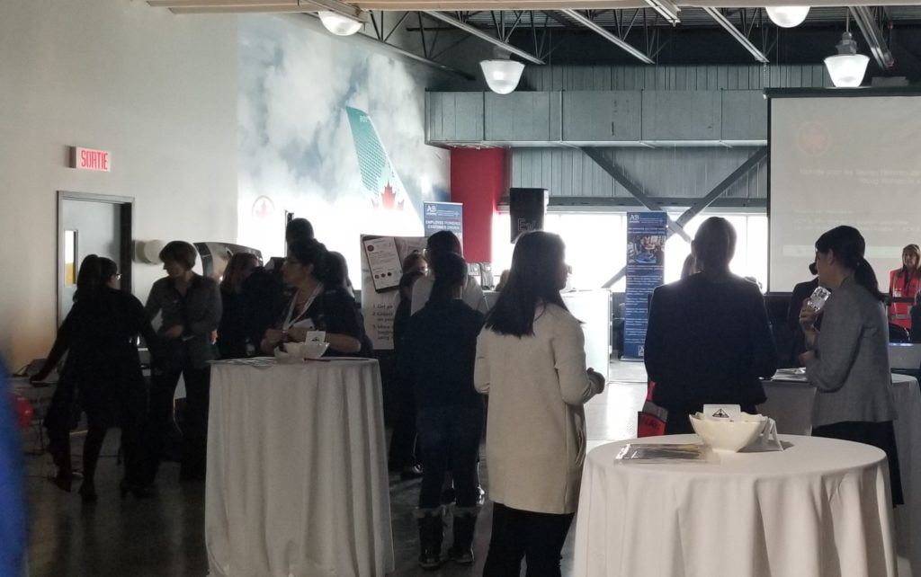 women standing up around tables listening to a presentation at Air Canada HQ