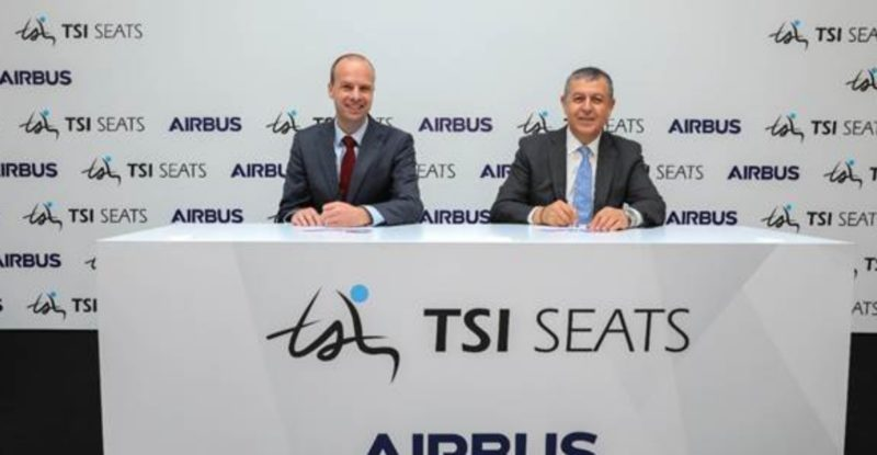 two men sitting at a table with a tsi and airbus logo on it