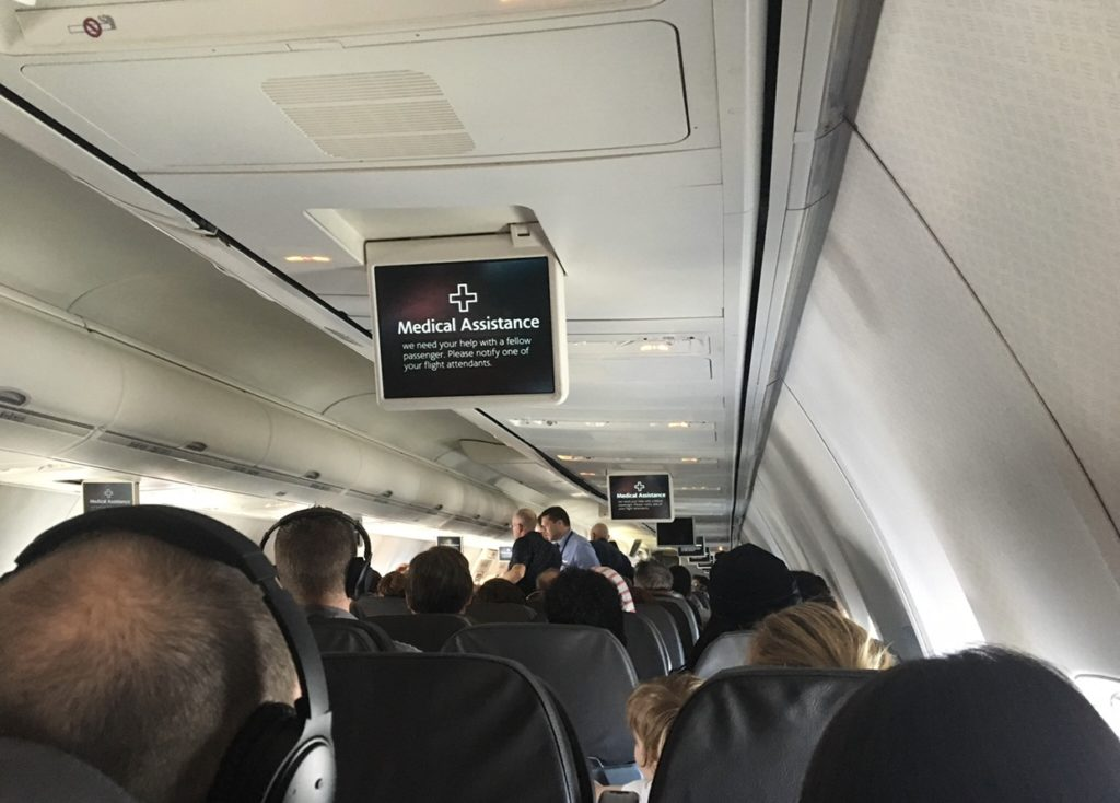"An American Airlines overhead screen, which alerts passengers that the crew needs ""Medical Assistance"" for a passenger on board"