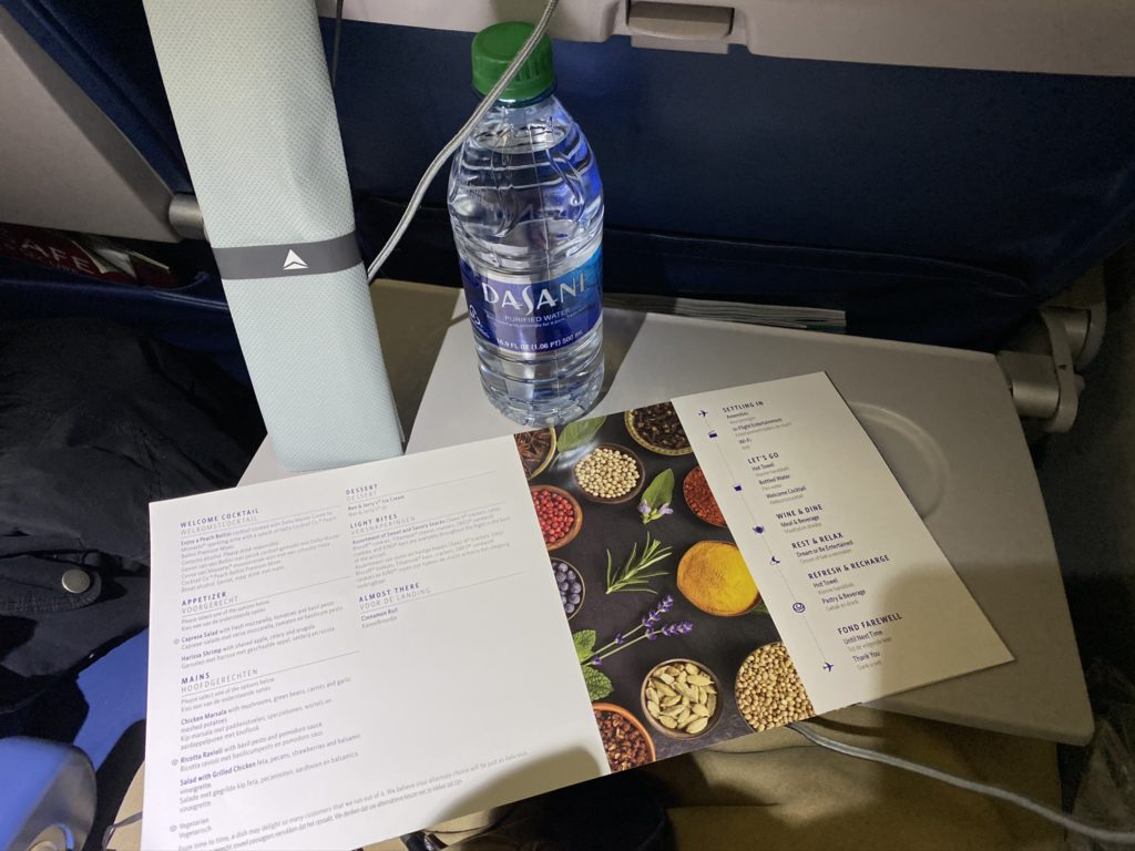 Menu, water bottle, and meal kit on aircraft tray table