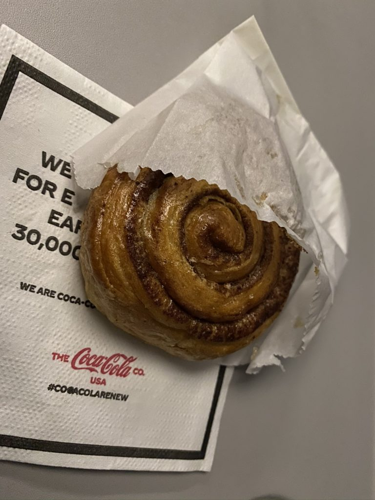 Cinnamon roll in a bag on aircraft tray table