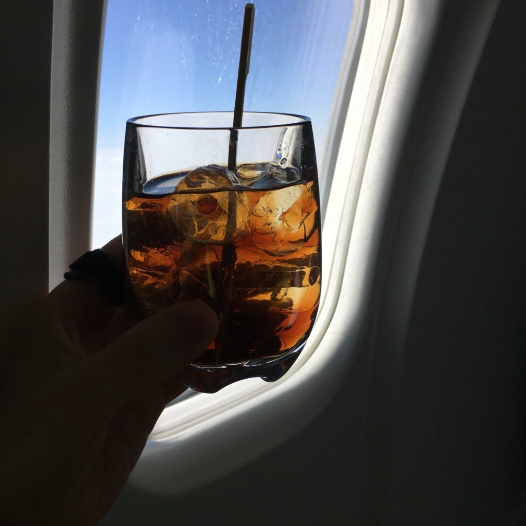 glass with drink and straw in front of aircraft window
