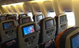 aicraft cabin interior showing IFE seatback