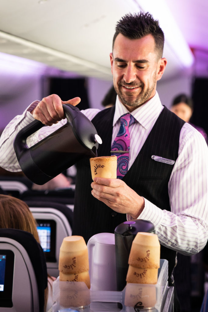 Air New Zealand flight attendant pouring coffee into an edible cup