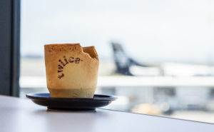 edible cup on table with blurred aircraft in the back