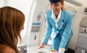 flight attendant serving a meal to a passenger inflight