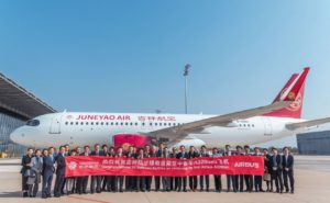 Group of people holding a banner in front of an aircraft