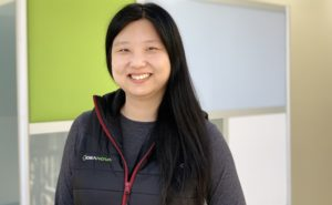 Tinglan Yang smiling with IdeaNova vest on and multi coloured squares in background