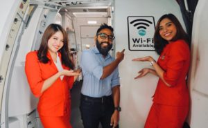 Two AirAsia female crew members and one male pointing to the WIFI now available sign on the aircraft entry way