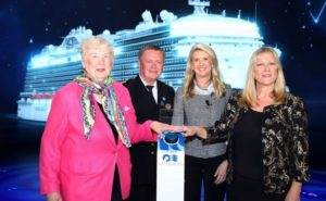 poppy with two other women and a man standing at a podium with a cruise ship in the backdrop