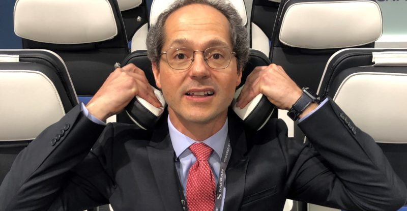 Safran executive demonstrates headrest pillow on new Z400 economy class seat