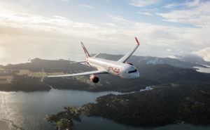 Air Canada Rouge aircraft flying over a scenic view
