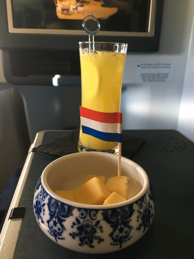 drink and cheese displayed on aircraft table