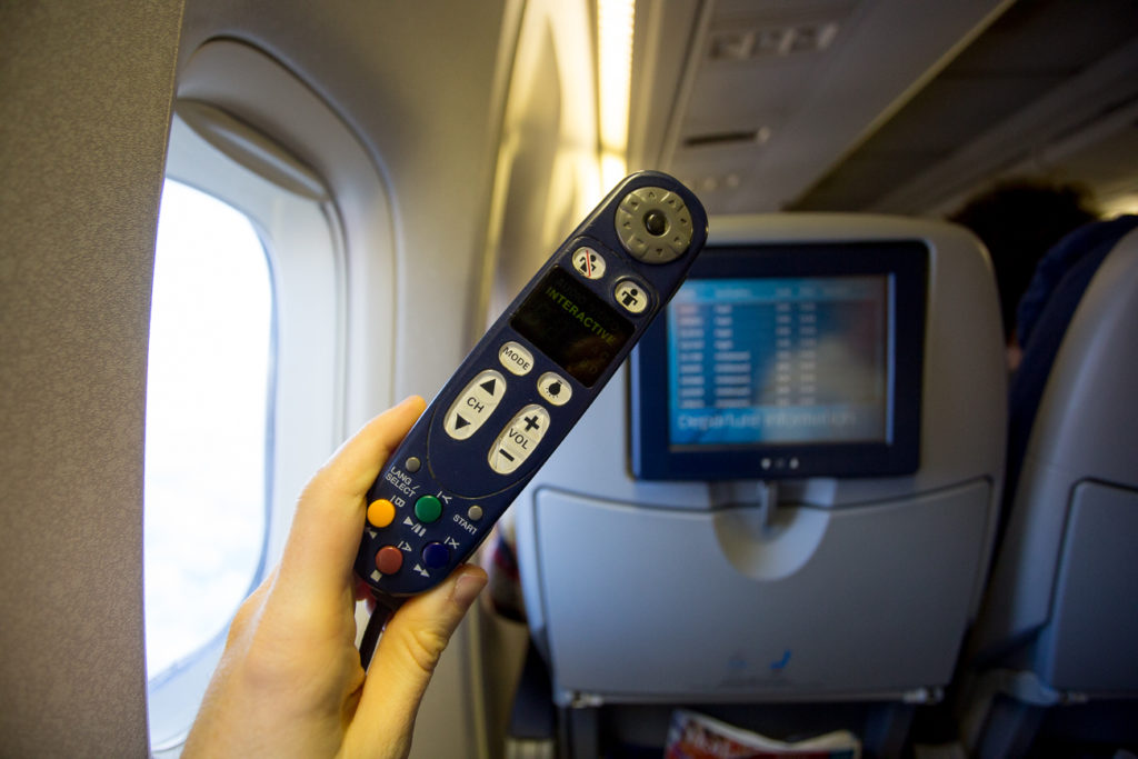 Remote that controls IFE being held up on aircraft