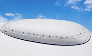 ThinKom's Ka antenna atop a regional jet fuselage. The antenna is quite slim in profile. A blue sky serves as the backdrop