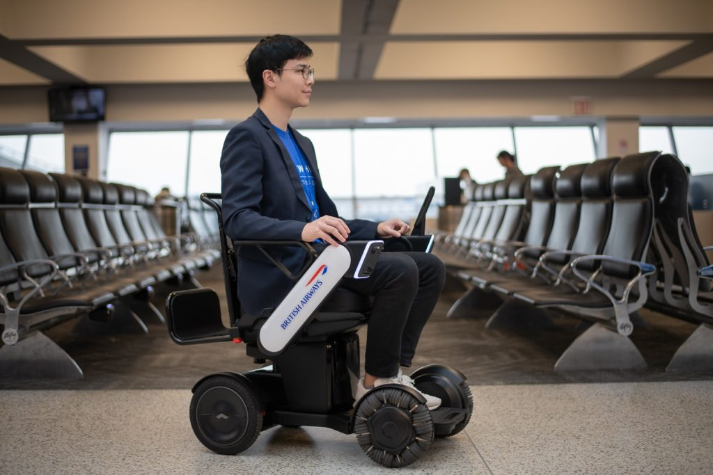 A man using the BA autonomous wheelchair in an airport terminal