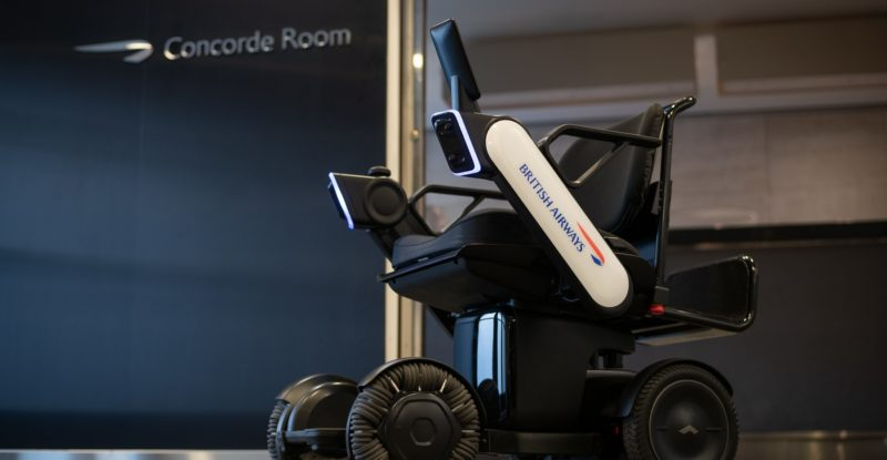 British Airways logo displayed on autonomous wheelchair sitting empty in front of the Concorde Roon sign on a blue wall