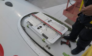 A technician installs Gilat's electronically steered antenna atop an aircraft fuselage. The antenna is flat and slim.