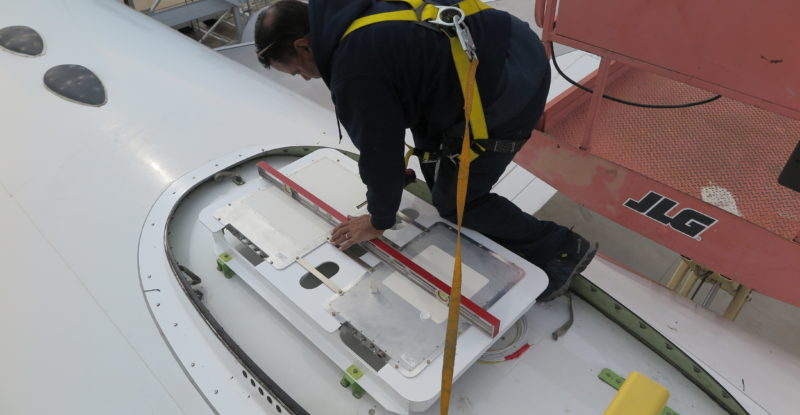 Gilat antenna being installed on the Honeywell 757 testbed aircraft. This photo shows a man on his knees, doing the installation