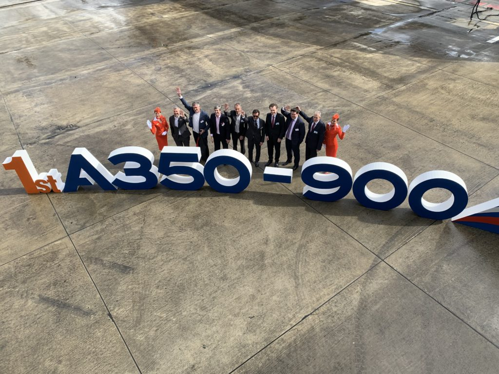 """An aerial photo of Aeroflot crew and a big sign saying """"1st A350-900"""""""