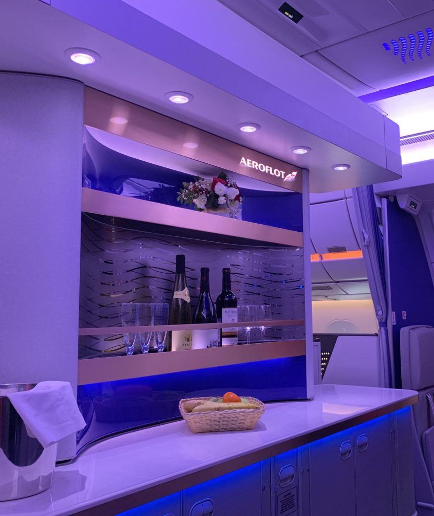 Business class bar in soft blue lighting stocked with different beverages and glasses
