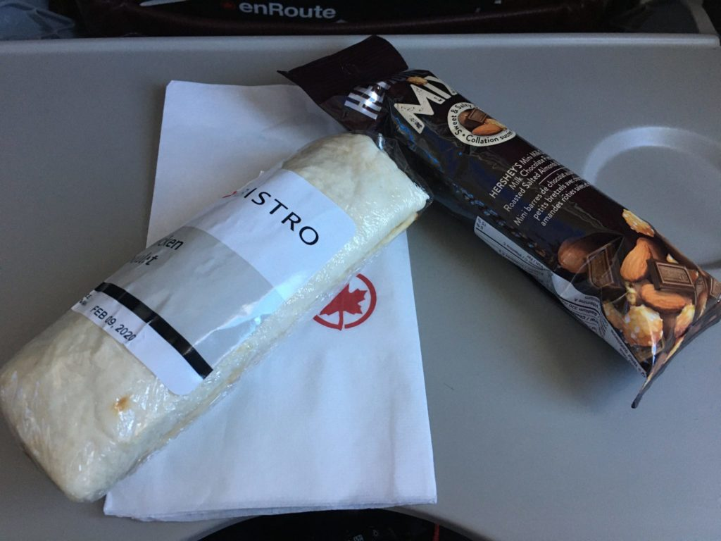 Bistro chicken wrap and Herseys snack mix displayed atop of an Air Canada napkin on tray table