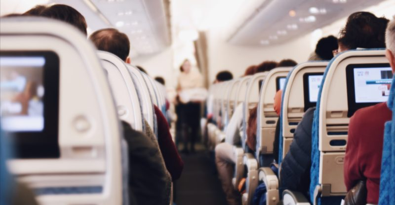 Seatback IFE screens in row after row of aircraft seats