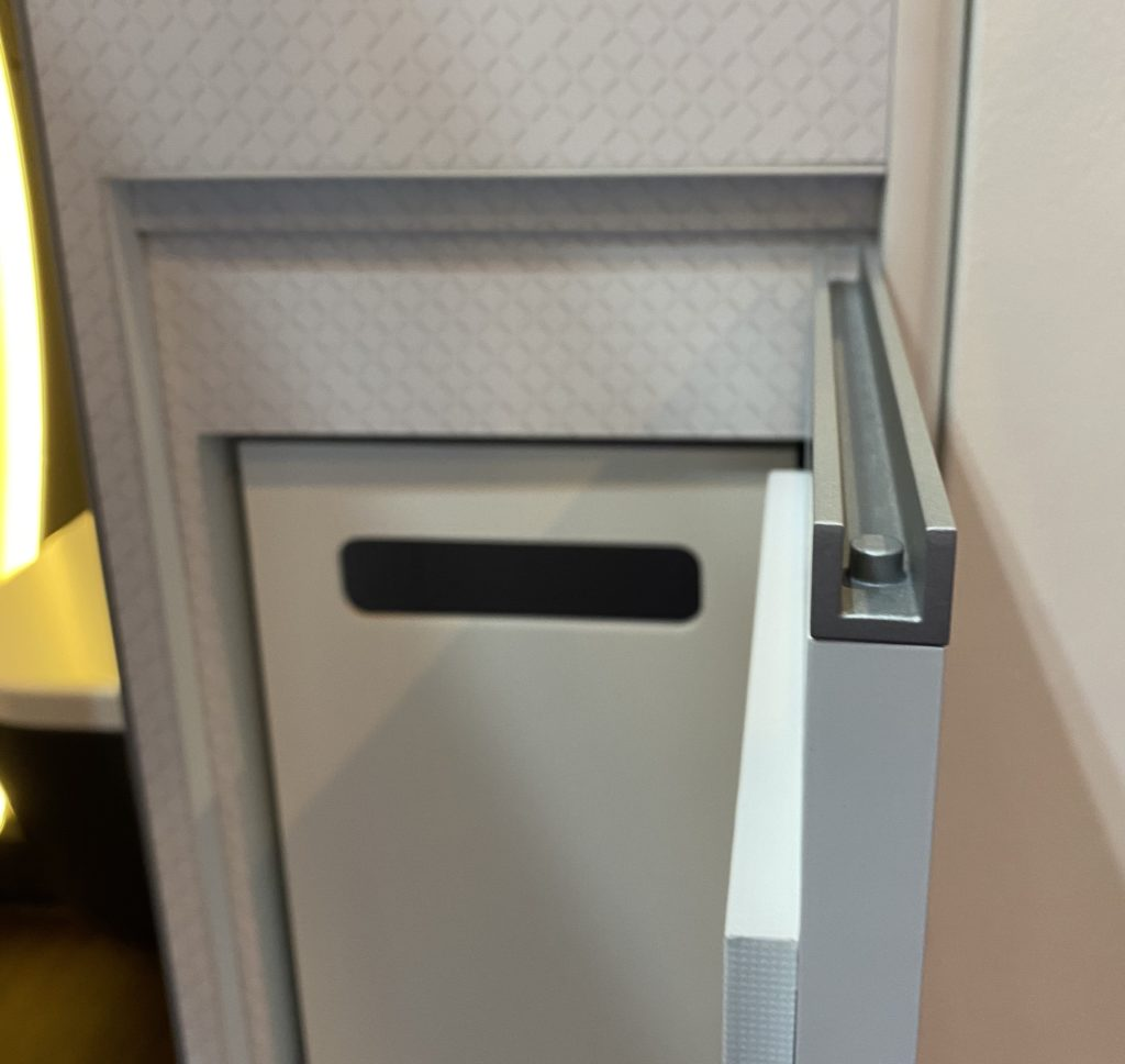A waste bin cubbie is shown here, with a simple lock mechanism. It slides out into the aisle