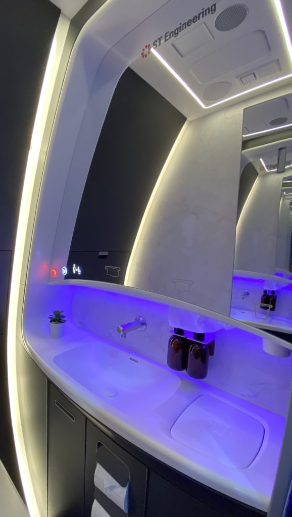 The sink deck slopes upwards and forms part of the sidewall. This image shows the slope, a cured mirror and purple LED lighting around the faucet fixtures