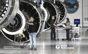 Workers at a Pratt & Whitney factory work on three large engines. Three engines are in view