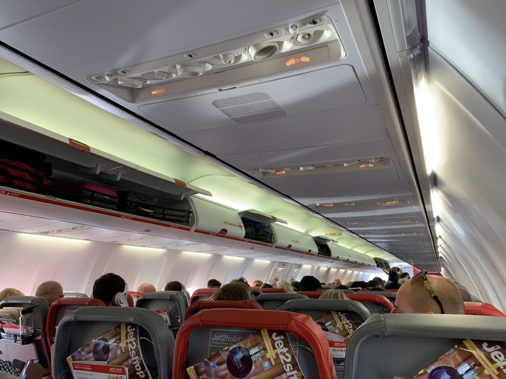 Overhead passenger service units aboard the Jet2 737. The seats are alternating grey and orange