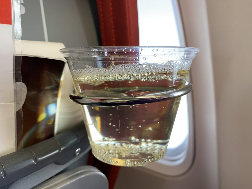 Sparkling wine in a plastic cup slotted into the seat cupholder