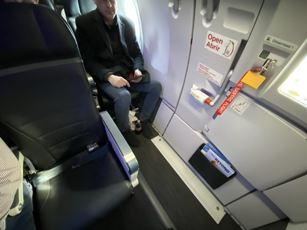 Alaska airlines interior showing exit row seating with a man in the seat behind
