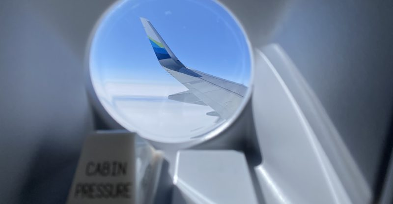 Looking out a circular aircraft window at the wing tip in the clouds with a cabin pressure box titled in front