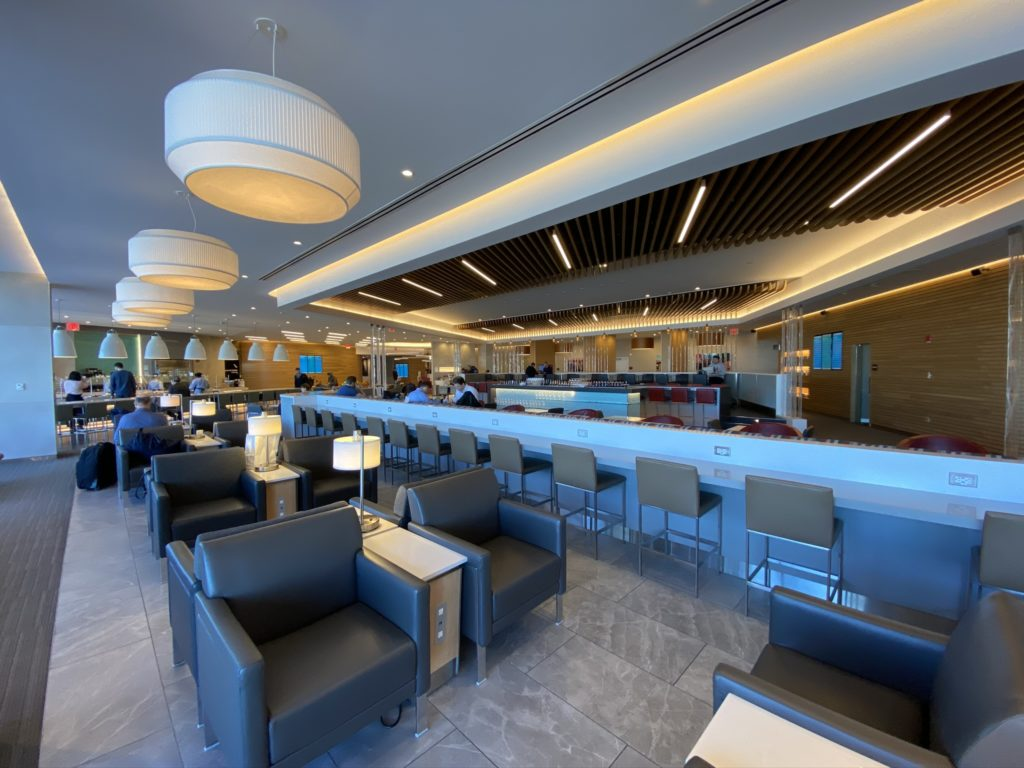 American Flagship Lounge with multplie seating options in grey leather and large white bowl like hanging lights