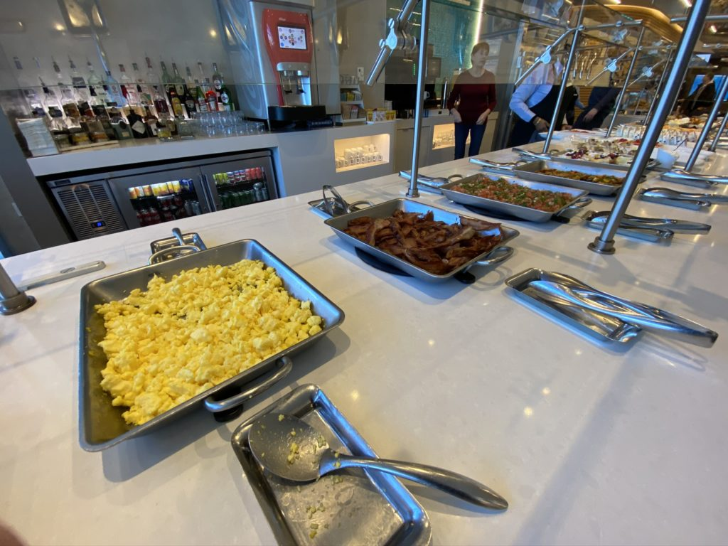 Beakfast buffet displayed showing scrambled eggs, bacon and other staples